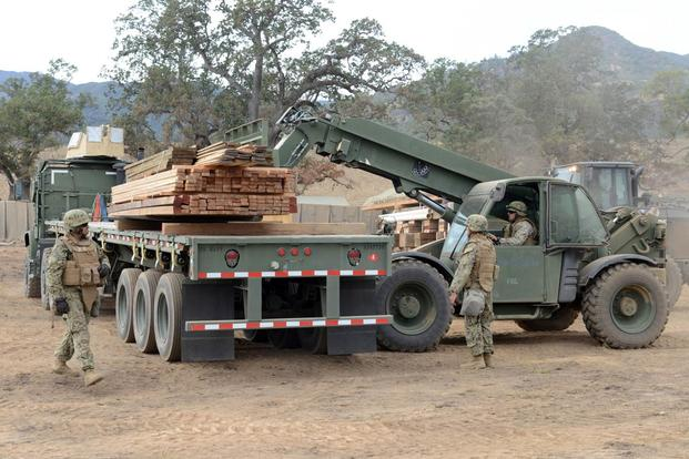 Seabees assigned to Naval Mobile Construction Battalion (NMCB) 4, unload pallets from a trailer during NMCB 4's field training exercise. (Photo: Mass Communication Specialist 1st Class Rosalie Chang)