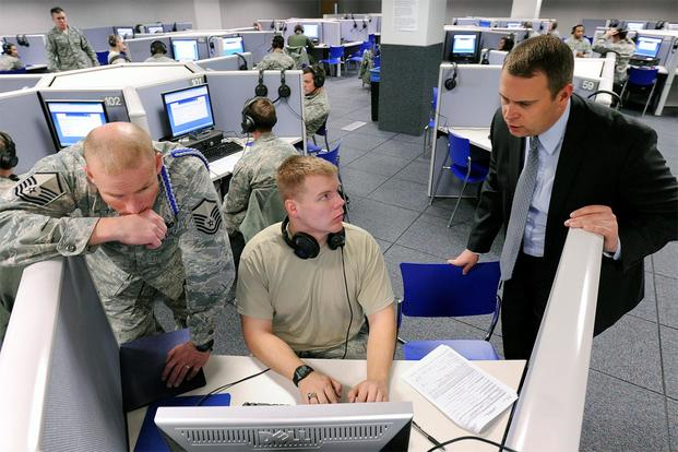 Master Sgt. Jesse Chervinka and Jessie Rhom help a cadet process an Electronic Questionnaire for Investigations Processing, or e-QIP, form in the Foreign Language Lab here Jan. 12, 2013. (U.S. Air Force photo: Mike Kaplan)