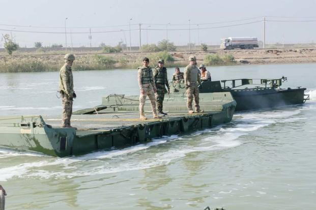 FILE PHOTO -- U.S. Army Soldiers with the 814th Multi-Role Bridging Company and Iraqi engineers with the 15th Iraqi Army Division, drive the MK-II bridge erection boat toward an improved ribbon bridge, Nov. 20, 2015. (Photo by Sgt. Cheryl Cox )