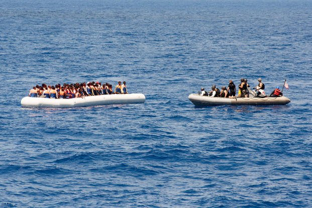 Sailors assigned to the USS Carney approach a small craft full of migrants while on patrol in the Mediterranean Sea on July 29, 2016. Senior Chief Personnel Specialist Galen Draper/Navy