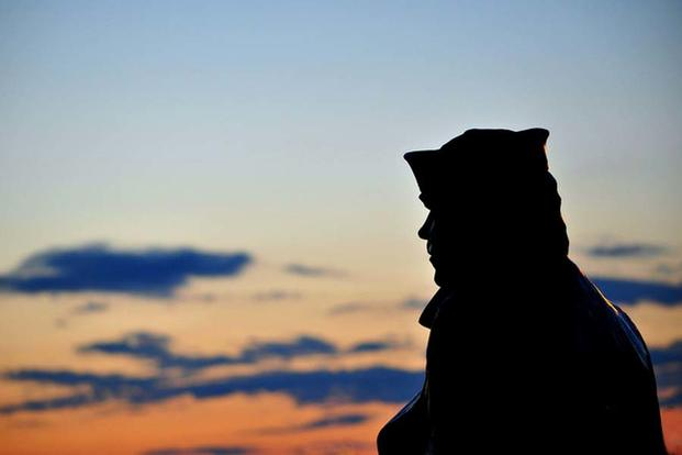 Sailor sits in contemplation as the sun sets. (Navy Photo)