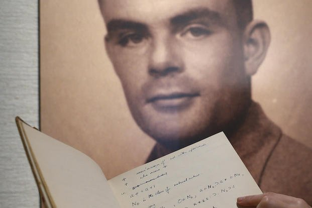 In this March 19, 2015, file photo, a page from the notebook of British mathematician and pioneer in computer science Alan Turing, the World War II code-breaking genius, is displayed in front of his portrait during an auction preview in Hong Kong.