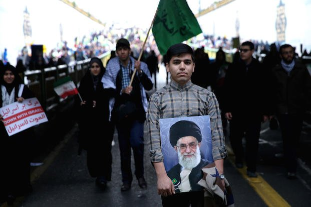 An Iranian man holds a portrait of Supreme Leader Ayatollah Ali Khamenei during a rally commemorating the 36th anniversary of Islamic Revolution under Azadi Tower, Tehran, Iran, Wednesday, Feb. 11, 2015.