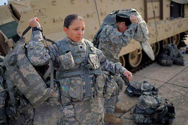 Spc. Karen Arvizu, left, puts on her hydration pack in preparation for her role as a volunteer in a physical demands study in Fort Stewart, Ga. (AP Photo/Stephen B. Morton)