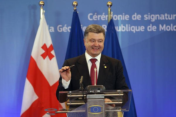 Ukrainian President Petro Poroshenko holds up a pen after a signing ceremony at an EU summit in Brussels on Friday, June 27, 2014.