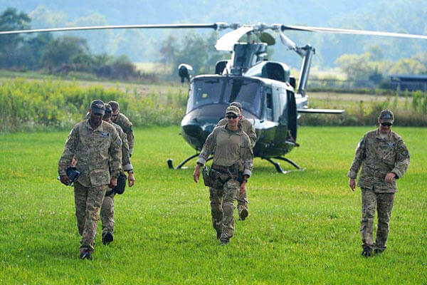 A team at the mobile command center in Deerfield, Va., walks away from a helicopter being used in a search and rescue mission to locate the missing pilot of an F-15C fighter jet August 27, 2014. Mike Tripp/The Staunton News Leader via AP