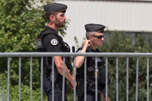 Police officers guard a road leading to a plant which was attacked on Friday in Saint-Quentin-Fallavier, southeast of Lyon, France, Saturday, June 27, 2015. (AP Photo/Michel Euler)