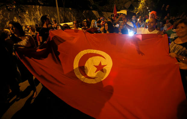People carry a Tunisian flag during an protest against terrorism in Sousse, Tunisia, Saturday, June 27, 2015. (AP Photo/Darko Vojinovic)
