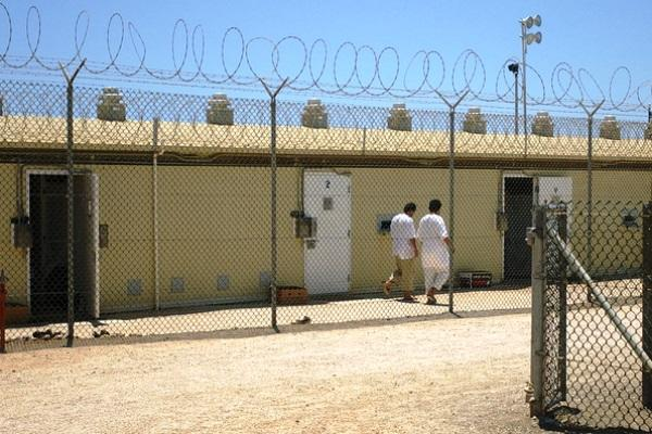 Detainees walk around an exercise yard in Camp 4, the medium-security facility within Camp Delta in 2006 at Naval Station Guantanamo Bay, Cuba. (Army photo by Sara Wood)
