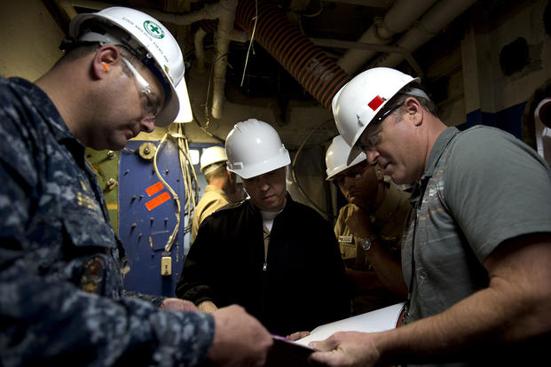 Cmdr. Steve Shedd, left, discusses blueprints for the Consolidated Afloat Networks and Enterprise Services (CANES) program with Capt. D.J. LeGoff, center, the CANES program manager. (U.S. Navy/MC3 Karolina A. Martinez)