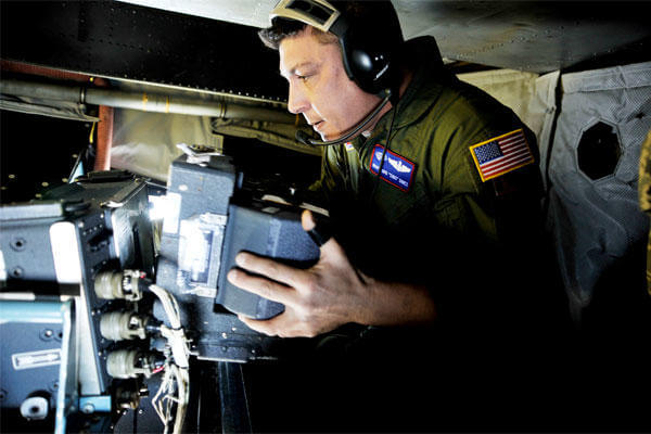 A crewman changes out film on board an OC-135B Open Skies observation aircraft. Another Open Skies plane made an emergency landing in Russia on July 27. (US Air Force/Perry Aston)