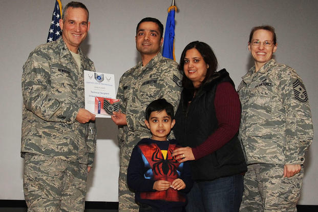 Staff Sgt. Vikas Kumar receives the STEP promotion to technical sergeant from Col. Brian Newberry, the 92nd Air Refueling Wing commander, and Chief Master Sgt. Wendy Hansen, the 92nd Air Refueling Wing command chief. (U.S. Air Force/A1C Sam Fogleman)
