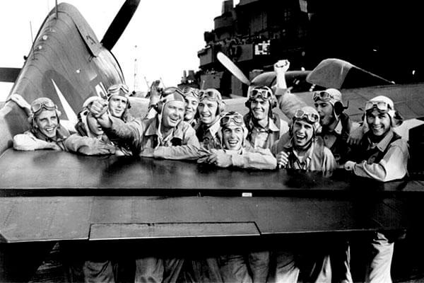 Pilots grin as they lean against the tail of a Grumman F6F Hellcat warplane on board the aircraft carrier USS Lexington. The personal accounts of thousands of World War II veterans are going online. (National Archives photo)