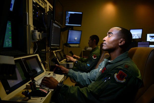 An MQ-9 Reaper pilot of the 432nd Aircraft Maintenance Squadron controls a drone from his work station at Creech Air Force Base, Nev. (US Air Force photo/Vernon Young, Jr.)