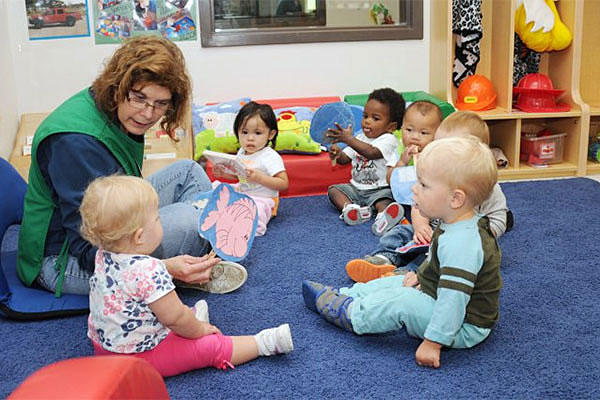 A military daycare worker read to children at a Fort Drum, New York, child development center. Michelle Kennedy/U.S. Army