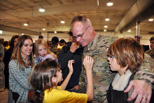 Sgt. 1st Class John Lemke, of the Wisconsin Army National Guard's B Battery, 1st Battalion, 121st Field Artillery Regiment, greets his family after a 10-month deployment to Afghanistan. (U.S. Army Photo)