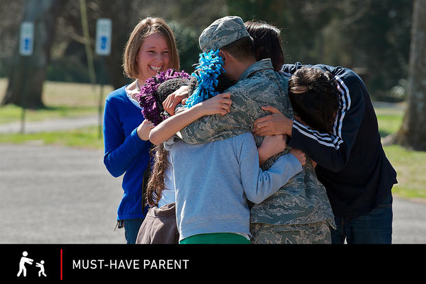 Carmen Villanueva watches as the Villanueva children mob their airman after he surprised them with his return from a one-year deployment. H. Andrew Hall/U.S. Air Force