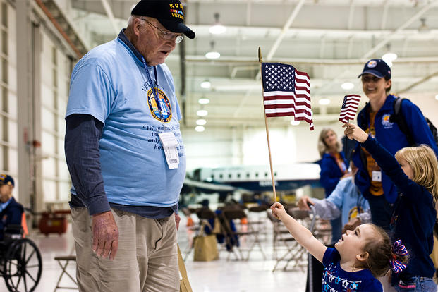 A child presents a U.S. flag to a Korean War veteran at the Denver International Airport. (Photo: U.S. Air Force/Airman 1st Class Riley Johnson.)