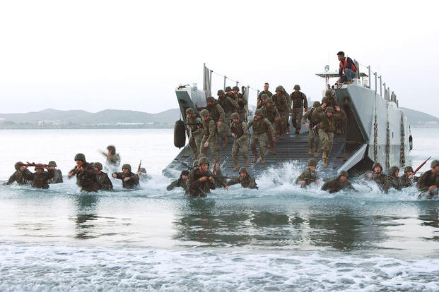 U.S. Marines and sailors assigned to the 1st Fleet Antiterrorism Security Team, 7th Platoon, jump out of their landing craft during a pre-dawn amphibious assault exercise (Petty Officer 1st class Terry W. Matlock, U.S. Navy. Released)