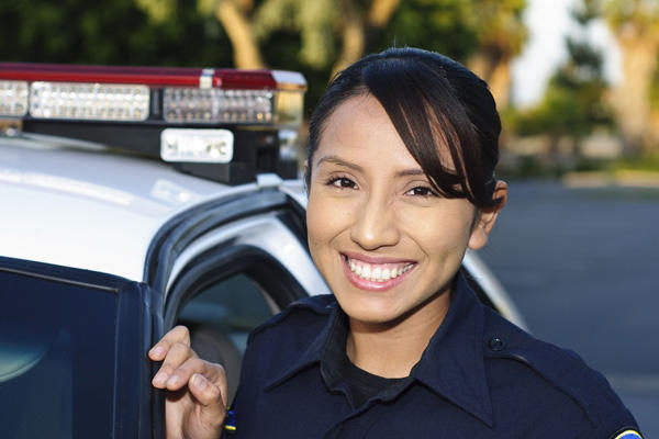 A young police officer standing next to her car.