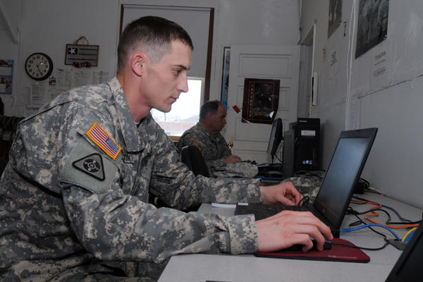 Servicemember using a laptop at a desk.