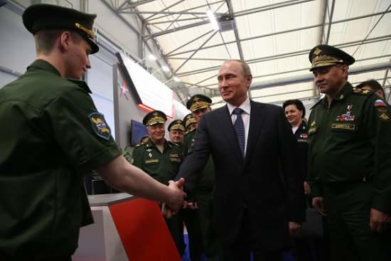 KUBINKA, RUSSIA - JUNE 16: Russian President Vladimir Putin (C) shakes hands with an officer as Defence Minister Sergei Shoigu (R) looks on during his visit to the International Military-Technical Forum ARMY-2015 at Patriot park June 16, 2015 n Kubinka, Russia. The forum is geared towards demonstrating capabilities of scientific organizations, defence industry businesses, weapons and equipment production, innovative technologies, both from Russia and abroad.  (Photo by Sasha Mordovets/Getty Images)