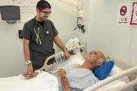 FILE -- Jonathan Serna, registered nurse, Surgical Ward, William Beaumont Army Medical Center, checks on Henrie Schneider, WBAMC inpatient, during Schneider's stay at WBAMC's Surgical Ward, April 11. (U.S. Army/Marcy Sanchez)