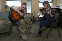 Army Staff Sgt. Sean Young strums the guitar during music therapy with Danielle Kalseth, 673rd Medical Operations Squadron creative arts and music therapist, at Joint Base Elmendorf-Richardson, Alaska, Nov. 2, 2017. (Air Force/Airman 1st Class Caitlin Russell)