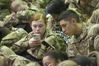 FILE -- Trainees check their cell phones and update their Family members at the Solomon Center on Fort Jackson Dec. 18, 2017 as they prepare to be processed for departure on Victory Block Leave (Fort Jackson Public Affairs Office/ Robert Timmons)