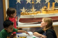 Laura Orr, deputy education director at Hampton Roads Naval Museum, teaches children about the exhibits during the launch of the 2016 Blue Star Museums program. (U.S. Navy/Amy M. Ressler)