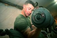 Lance Cpl. Christopher Talbot, with 2nd Light Armored Reconnaissance Battalion, curls a 50-pound dumbbell in Iraq. The Marine Corps will soon begin handing out awards for superior physical fitness. (Cpl. Ryan Tomlinson/Marine Corps)