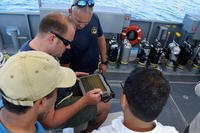Force Master Diver Scott Brodeur, Naval Expeditionary Combat Command, watches as Chief Navy Diver Marshall Goble tries out the Office of Naval Research (ONR) TechSolutions-sponsored Scuba Binary Dive Application (SBDA 100) during a demonstration and evaluation off the coast of Panama City, Fla., Aug. 7, 2018. (U.S. Navy photo/Bobby Cummings)
