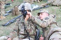 Spc. Collin A. Miller assists Pfc.l Lushell J. Hightower with adjusting Night Vision Goggles, Camp Grayling Joint Maneuver Training Center, June 9, 2018. (U.S. Army photo/Savannah Lang)