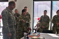 Spc. Ashley Hartman cuts the ceremonial birthday cake for the National Guard's 381st birthday alongside Nevada Adjutant General, Brig. Gen. William Burks, left. The Nevada National Guard Joint Forces Headquarters office celebrates the National Guard's birthday every year with the highest and most junior ranking members available as cake cutters. (Photo Credit: 2nd Lt. Emerson Marcus)
