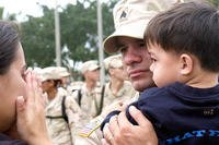 Military family, servicemember holding child.