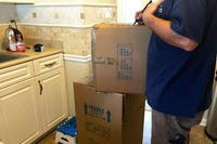 moving boxes in kitchen with mover