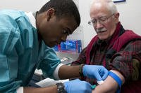 Airman 1st Class Luvens Rorshack draws blood from retired Army chaplain John Rasmussen in the Medical Treatment Facility on F.E. Warren Air Force Base, April 18, 2015. (U.S. Air Force photo/Airman 1st Class Malcolm Mayfield)