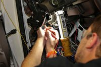 Mechanic working on a car's starting system.