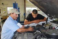 Two men repairing an engine in a garage.