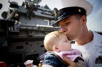 A sailor holding and kissing his child.