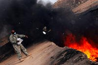 An Air Force master sergeant tosses unserviceable uniform items into a burn pit at Balad Air Base, Iraq on March 10, 2008. (US Air Force photo/Julianne Showalter)