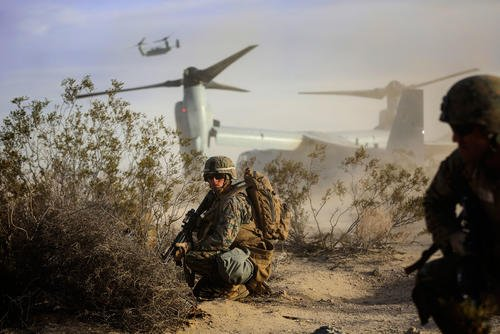 Cpl. Paul Regotti, a squad leader with 3rd Battalion, 7th Marine Regiment, provides security for Marines exiting an MV-22 Osprey during an air assault on a Military Operation on Urbanized Terrain town. The training was part of the Marine Corps' Combat Readiness Evaluation Exercise, Jan. 16, 2015. (U.S. Marine Corps photo/Julio McGraw)