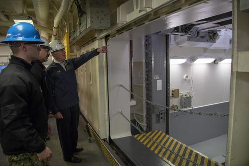Secretary of the Navy Richard V. Spencer is briefed by Lt. Cmdr. Chabonnie Alexander, USS Gerald R. Ford's ordnance handling officer, on the advanced weapons elevator during a tour of the carrier, Jan. 17, 2018. (U.S. Navy/Mass Communication Specialist 2nd Class Kiana A. Raines)